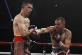 Rios of the U.S. takes a punch from compatriot Alvarado during a super lightweight bout for an interim 140lb WBO title in Las Vegas