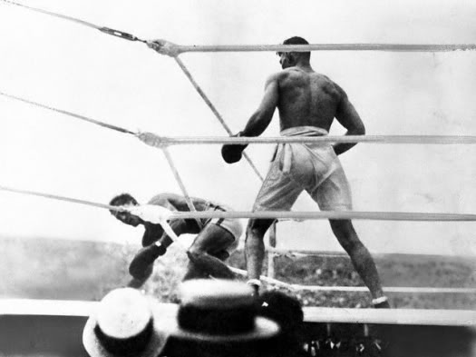 Carpentier is driven through the ropes by the fury of Dempsey's attack.